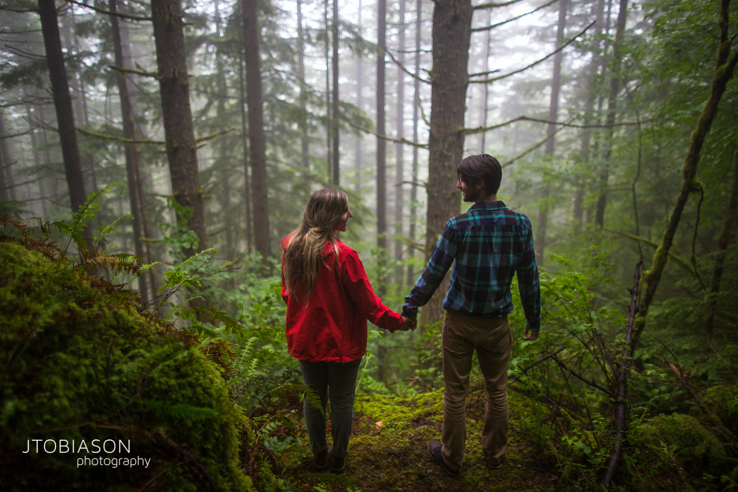 couple holds hands in the forrest photo
