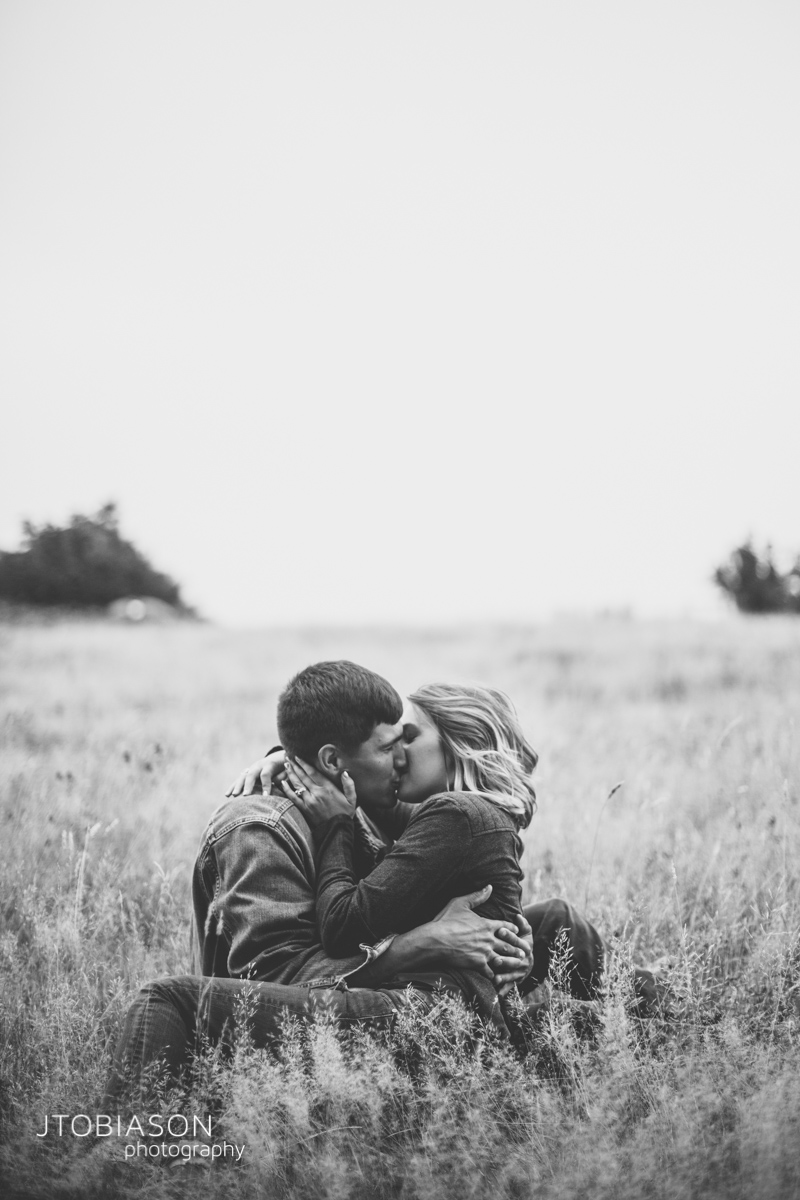 Couple kiss in field Discovery Park Engagement photo