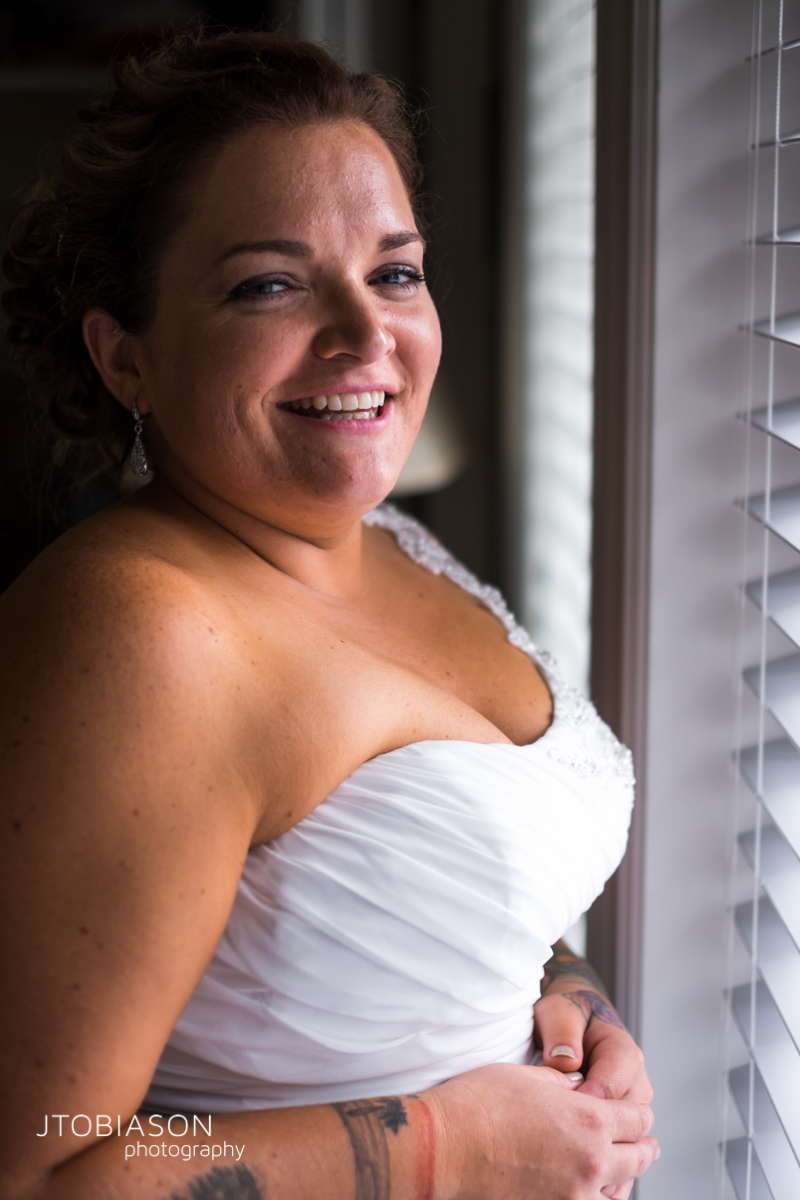 Bride stands by the window photo
