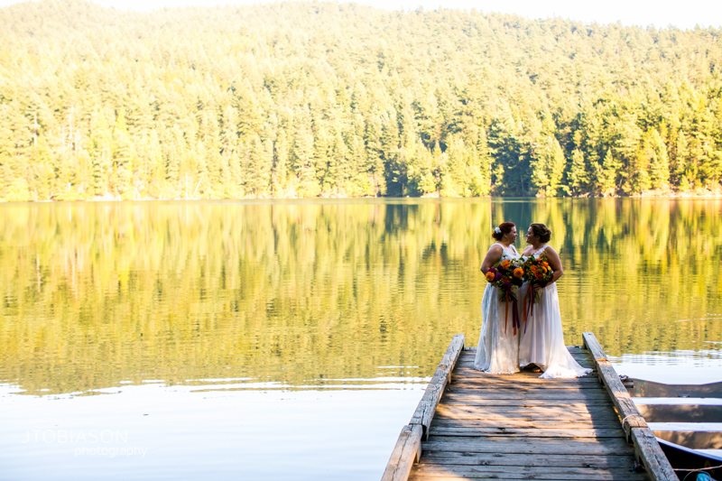 brides kiss at mountain lake photo