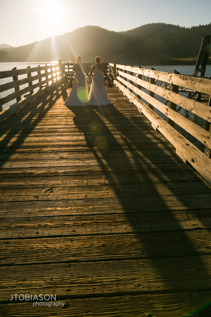 Brides walk down pier photo