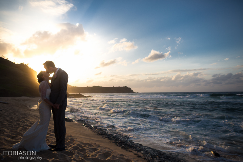 couple kisses on beach kauai destination wedding