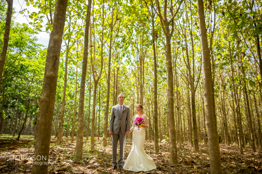 Bride and Groom stand in the woods Na 'Aina Kai Kauai Beach Wedding photo