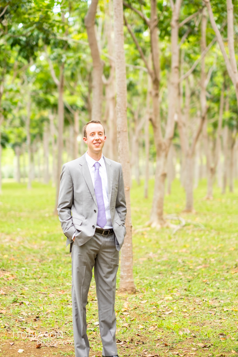 Groom stands in forrest photo