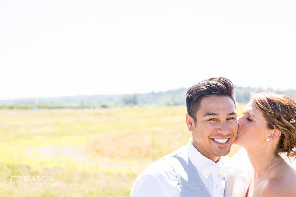 Bride and groom kiss in field at Dariyland Wedding photo