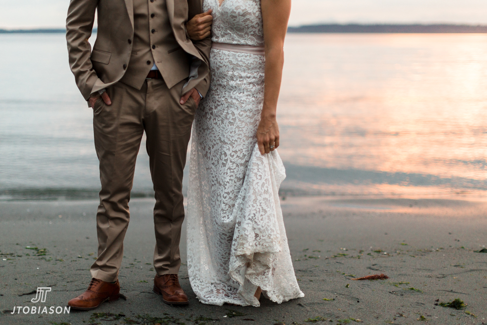 bride stand on the beach in the sunse golden gardens boathouse wedding