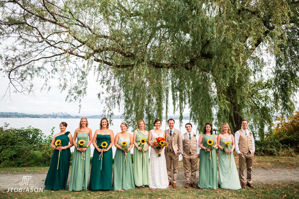 Wedding party smiles by water golden gardens boathouse wedding