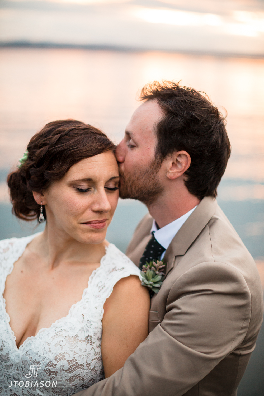 Groom kisses bride in sunset golden gardens boathouse wedding