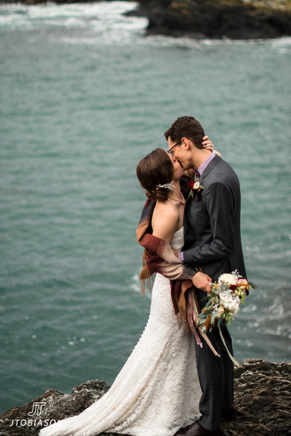 bride and groom kiss by water