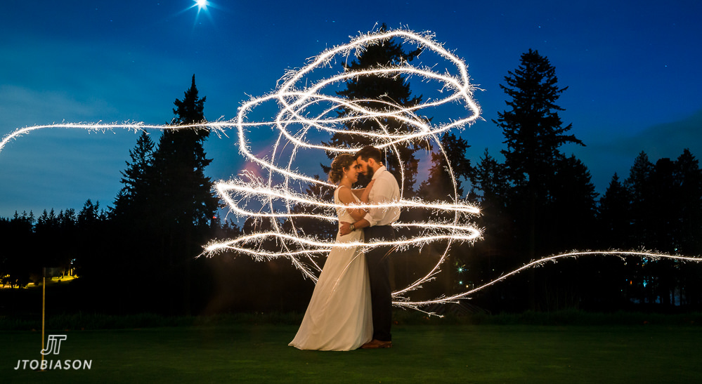 couple kisses under sparklers nile golf course wedding