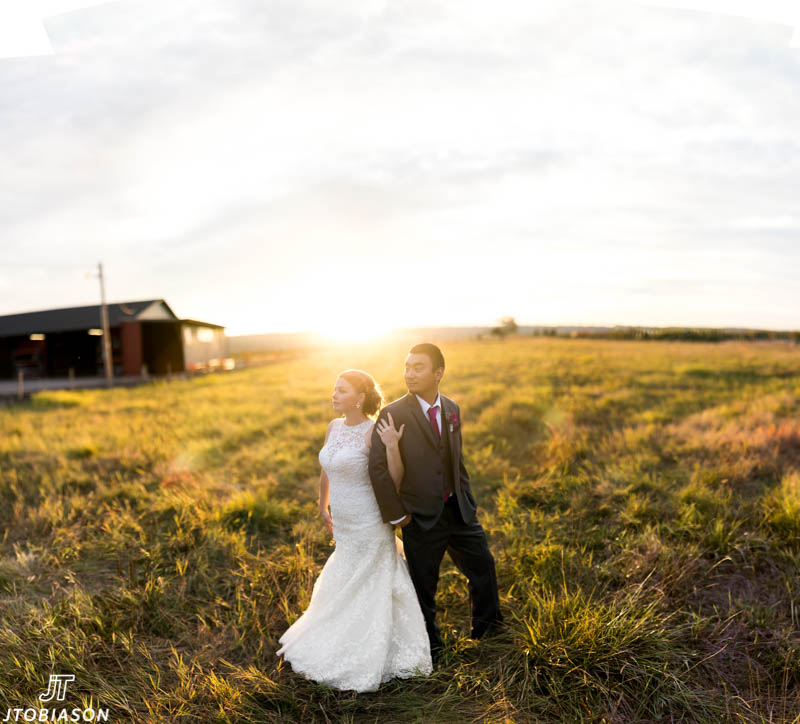 couple stands in the sunset hidden meadows wedding