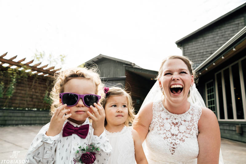 bride laughs with kids at wedding