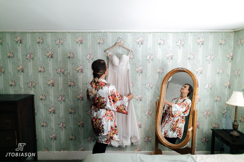 bride looks at bhldn dress brown family homestead wedding