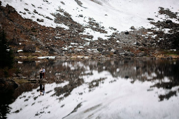 Couple stand in reflection Lake 22 Engagement photo