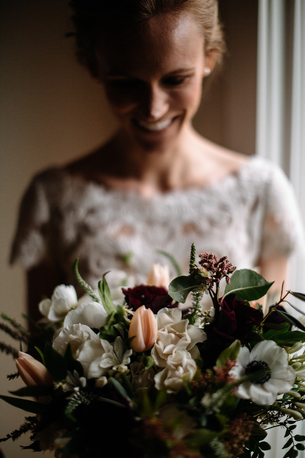 bride smiles at wedding bouquet