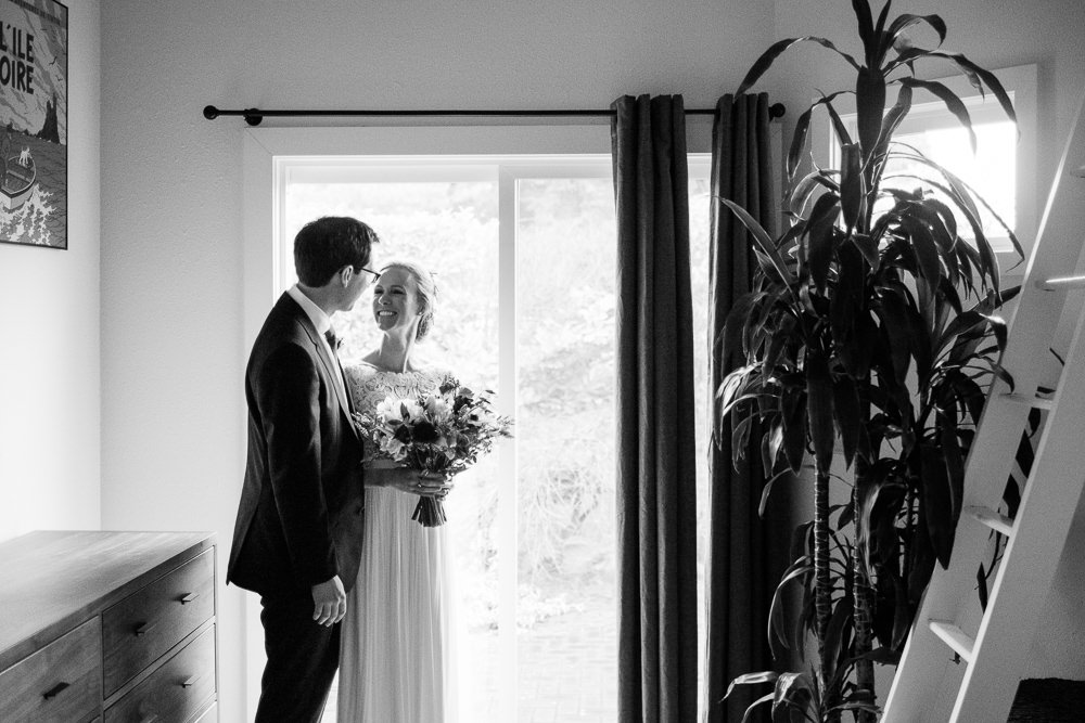 bride and groom smile in sliding door