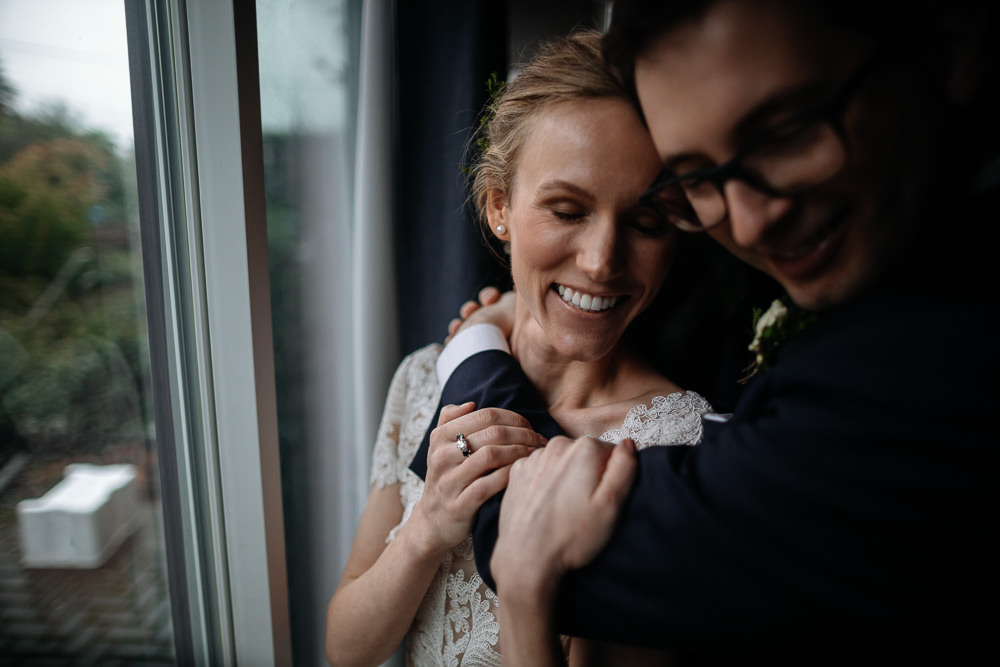 groom holds bride close