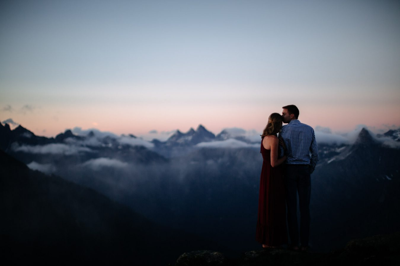 Couple looks off at mountains during sunset engagement