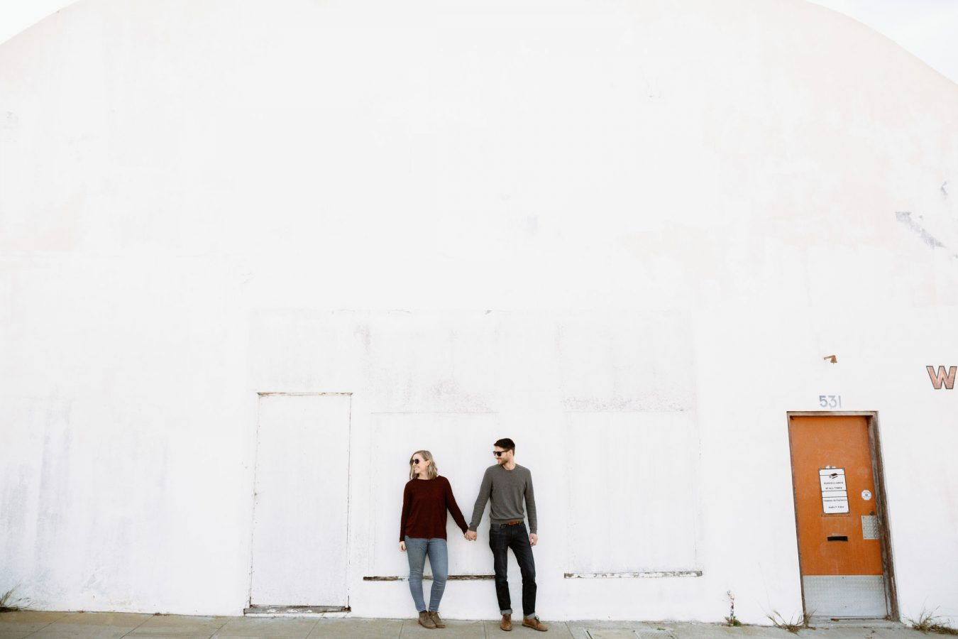 Couple holds hand next to white wall Los Angeles sunset engagement