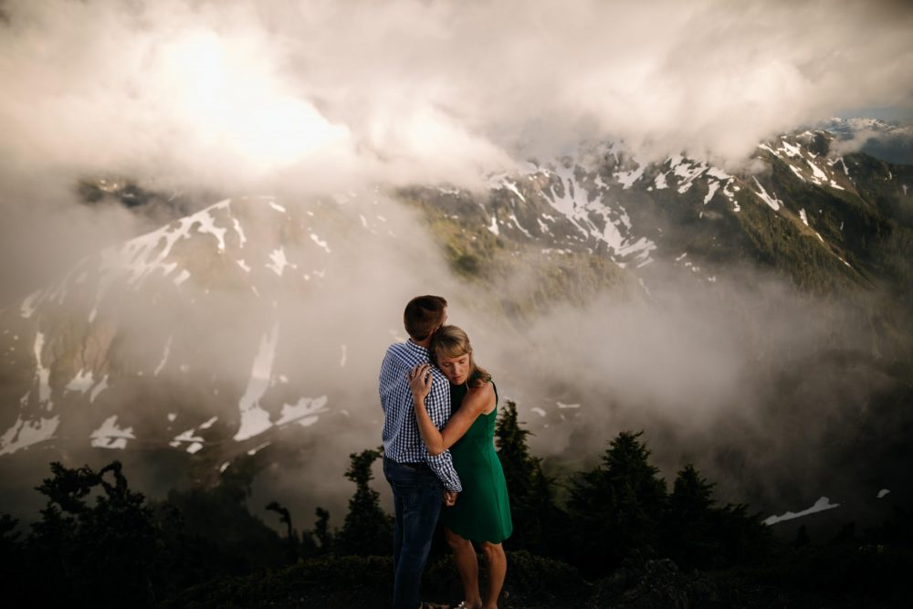 Couple hugs on top of mountaintop engagement