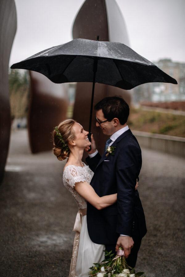 couple smiles under umbrellay rainy downtown seattle elopement