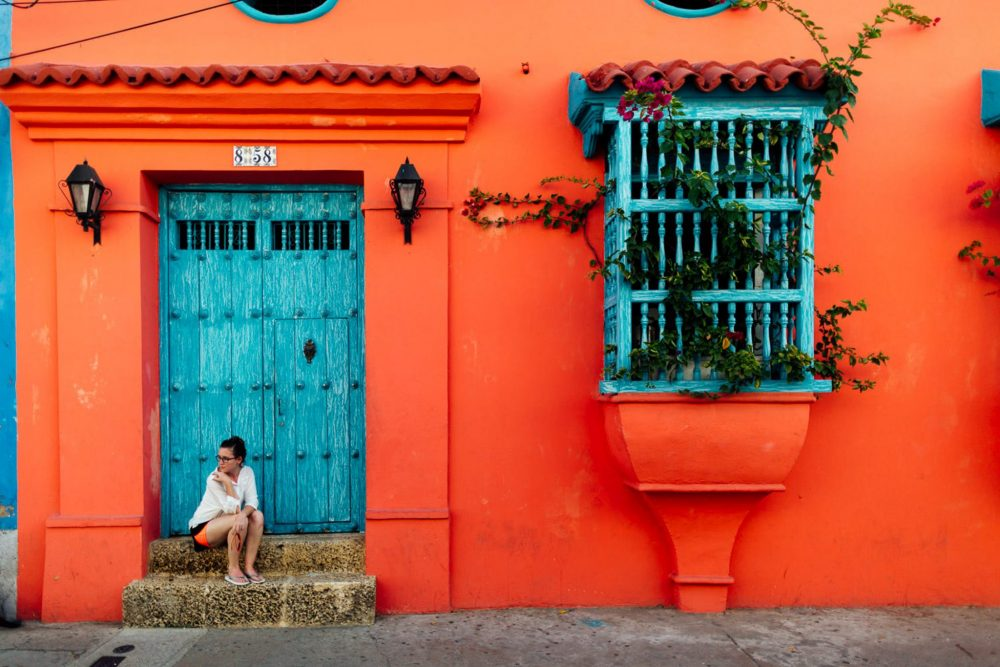 Woman sits on stairs in Cartagena Colombia