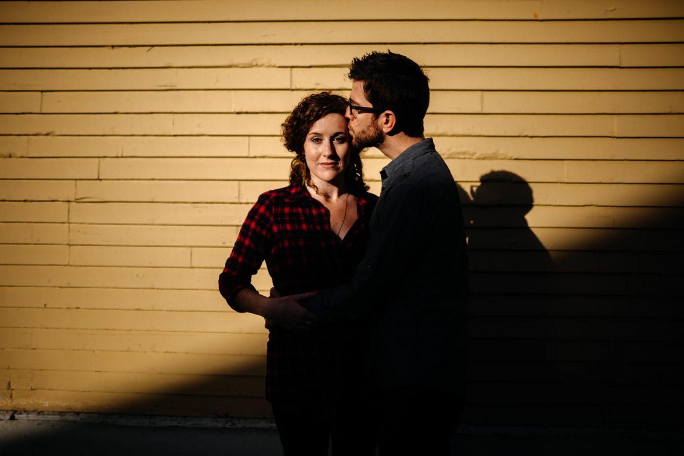 man kisses woman sunrise engagement