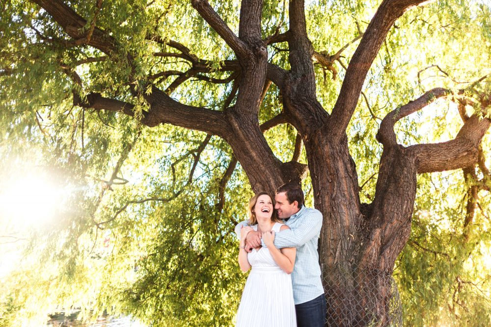 man and woman laugh in sun under a tree MOHAI engagement shoot