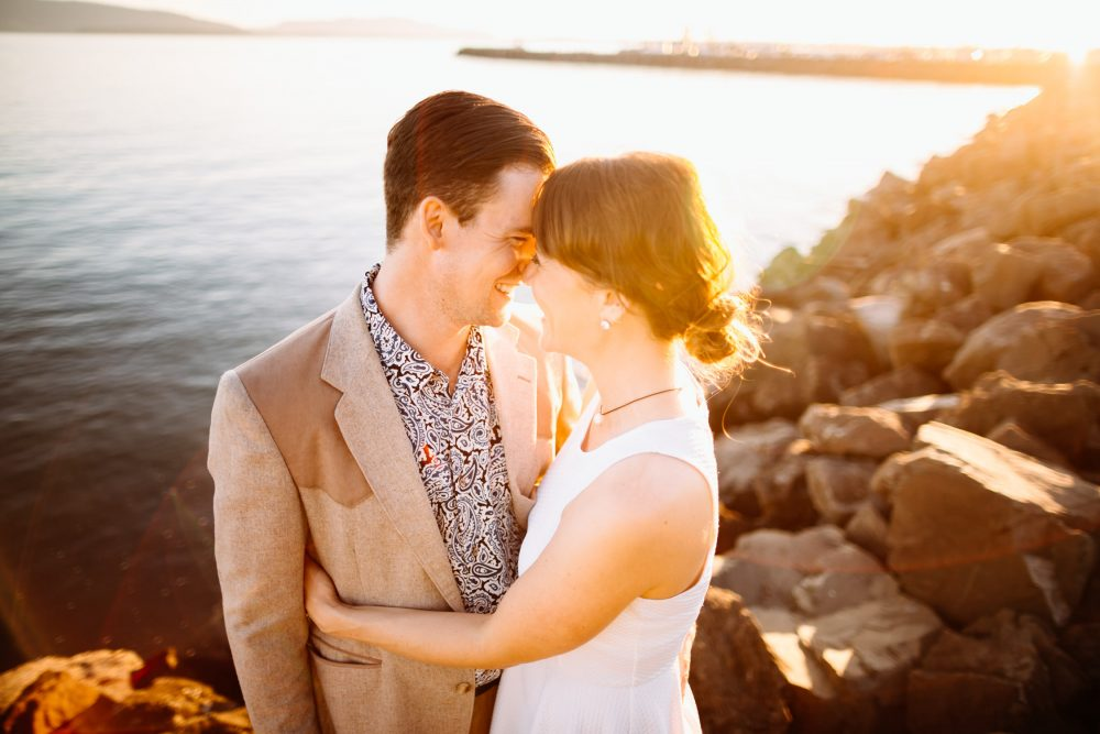 man and woman stand together bellingham sunset engagement