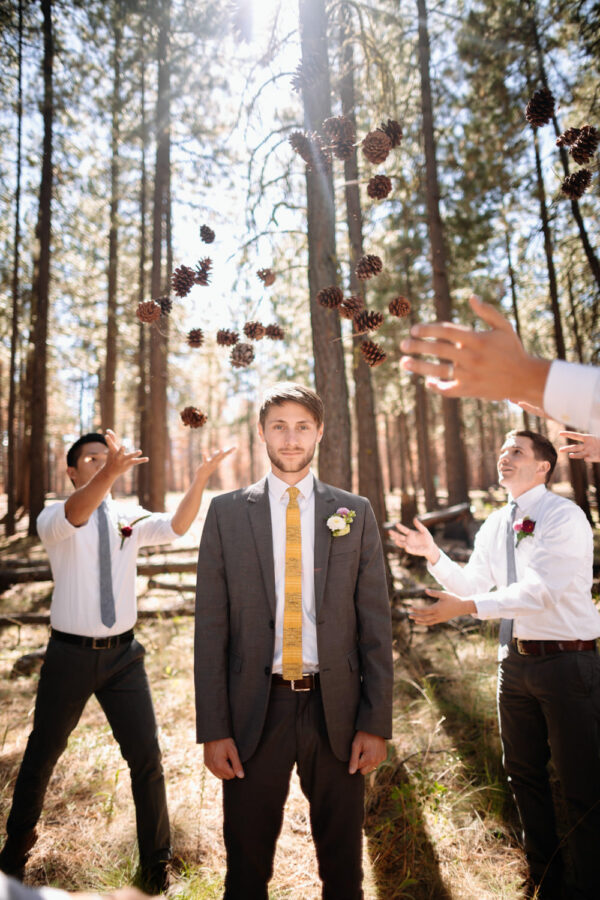 groomsmen throw pine cones at groom sisters oregon wedding