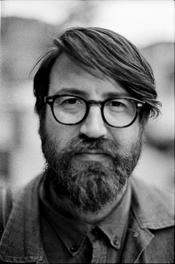 black and white portrait of man with bead and glasses in new york city