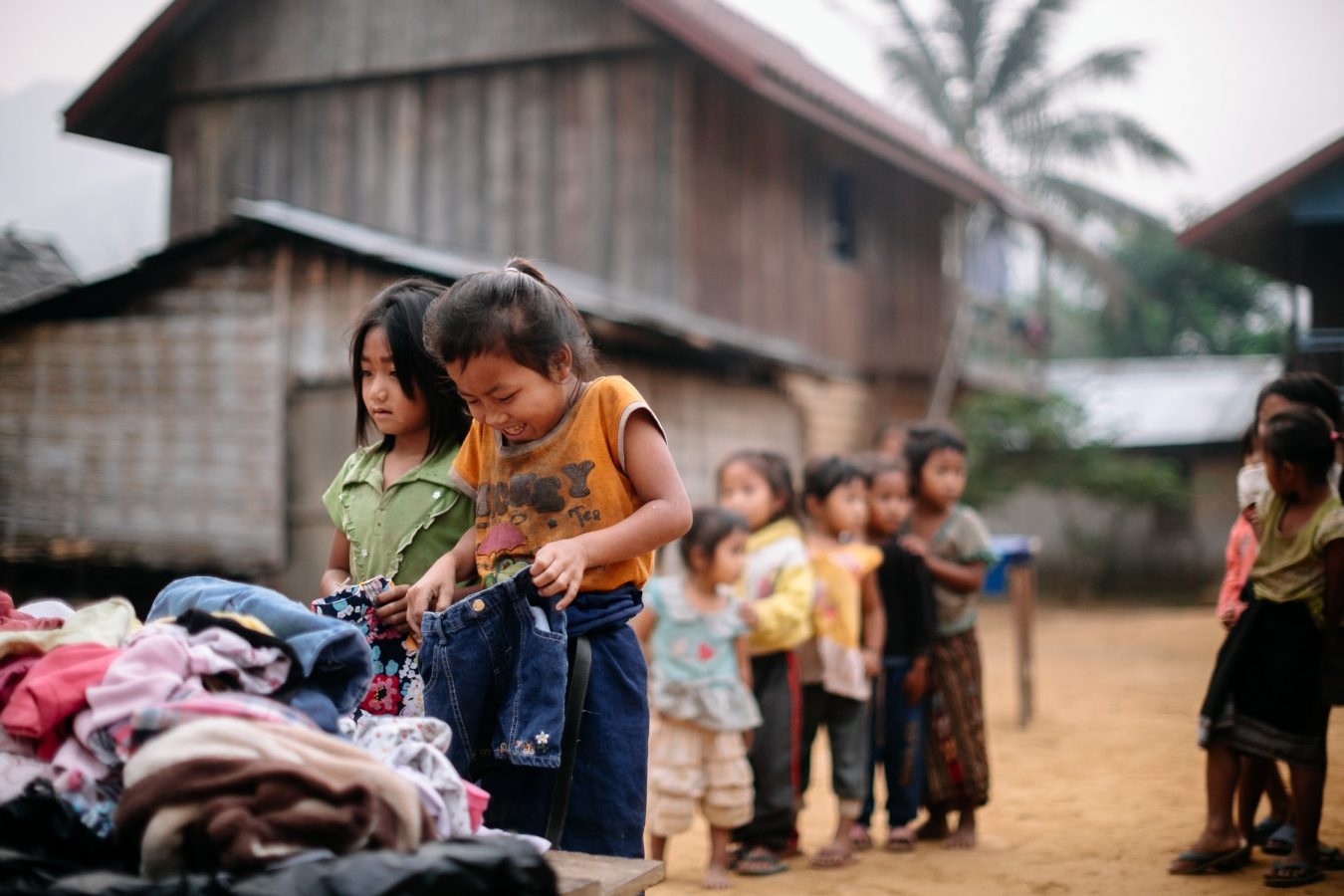 little girl picks out jeans and smiles in Laos photo