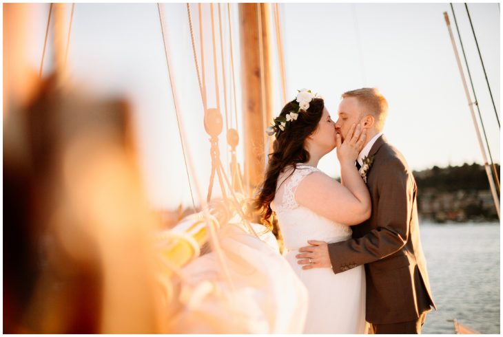bride and groom kiss on sailboat in sunset center for wooden boats wedding seattle