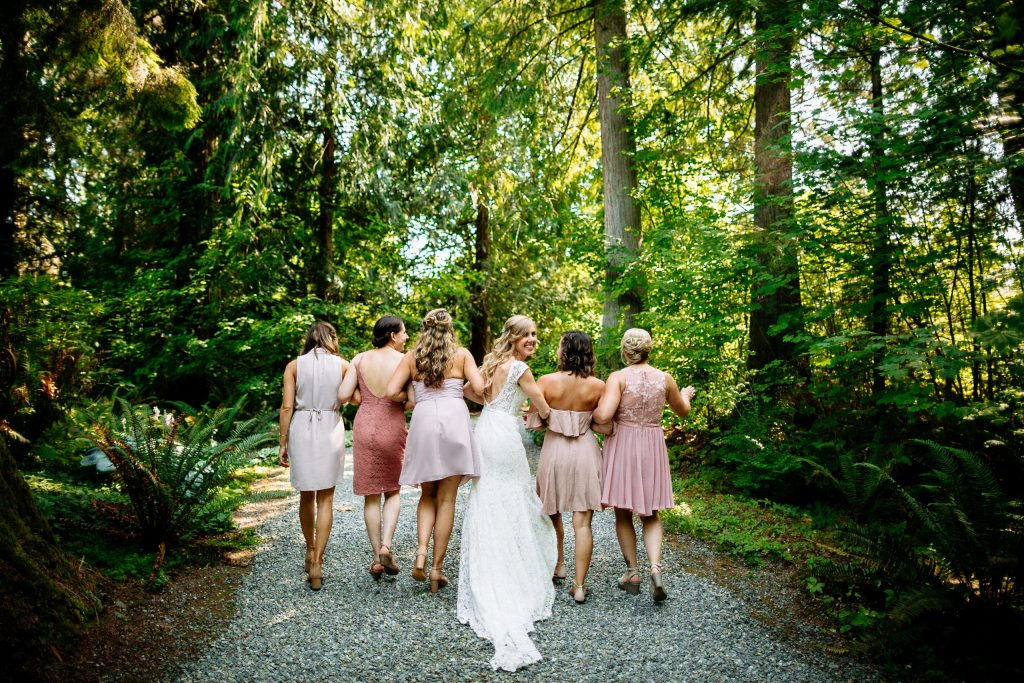 Bride and bridesmaids walk together in the woods before backyard elopement