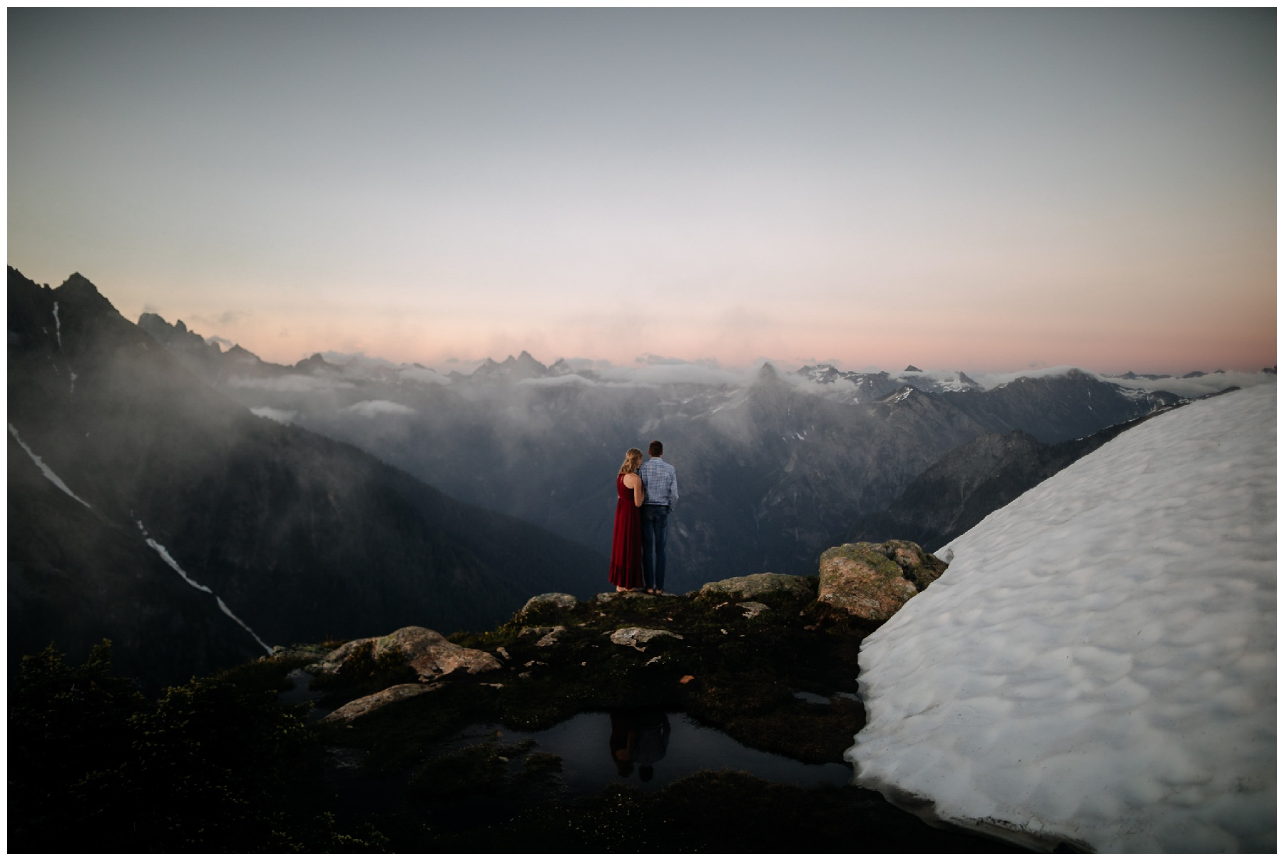 couple kisses during cascade mountaintop sunset engagement