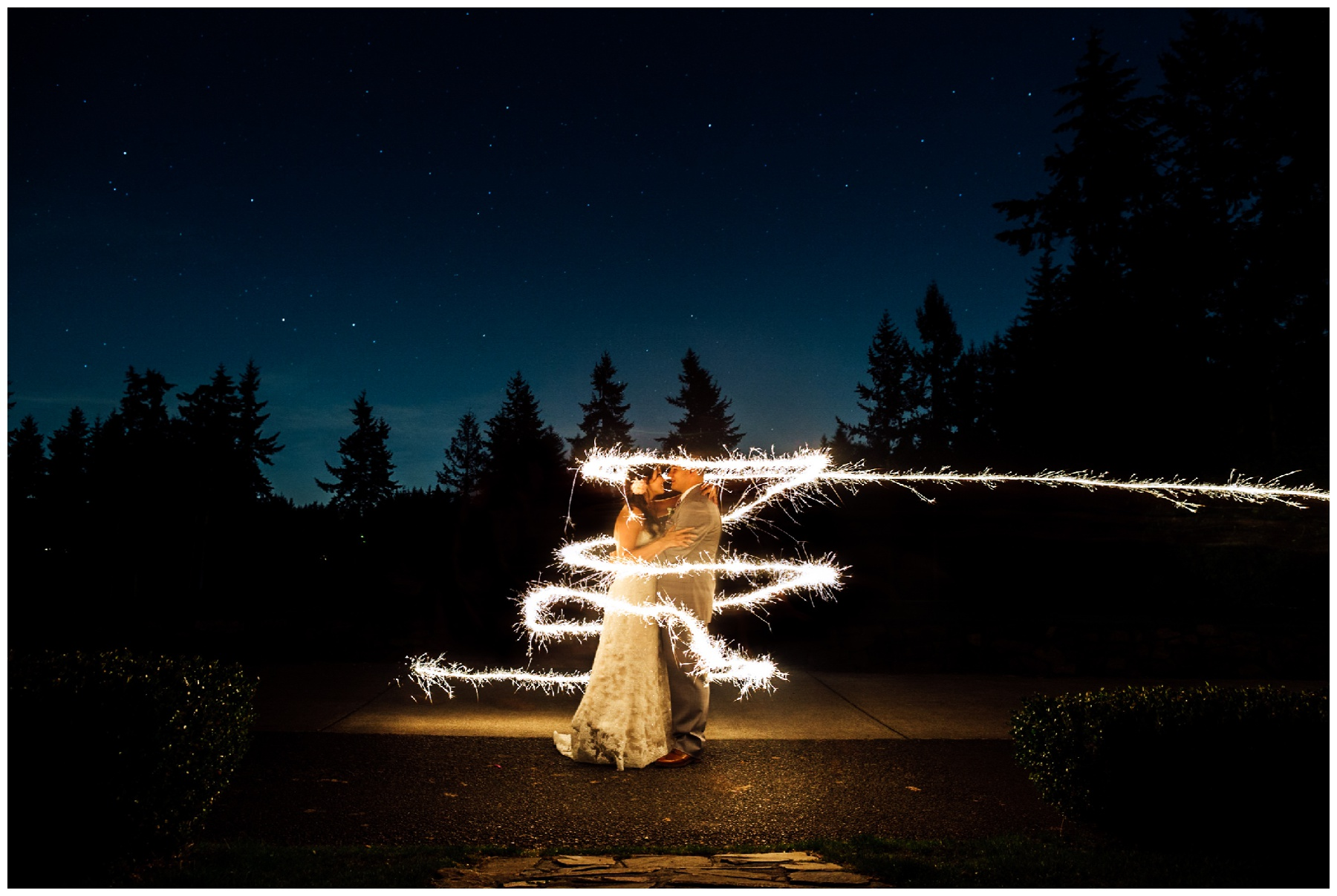 couple stands with sparkler around them