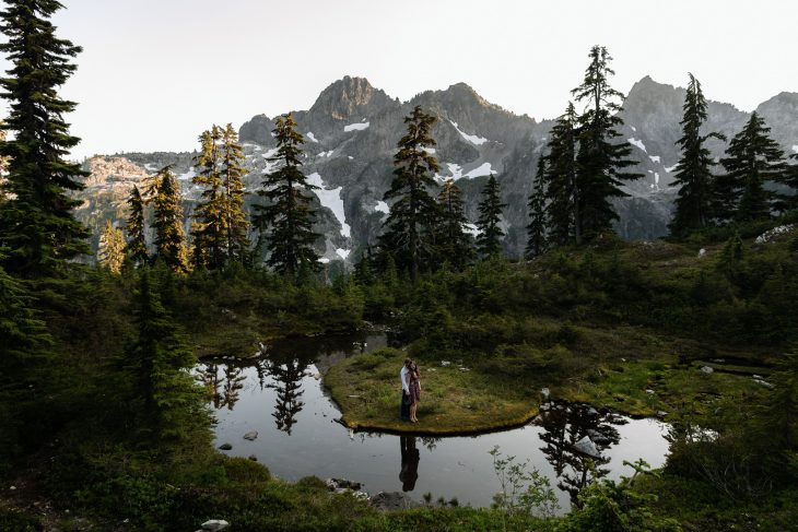 Couple poses by reflecting pond PNW hiking engagement