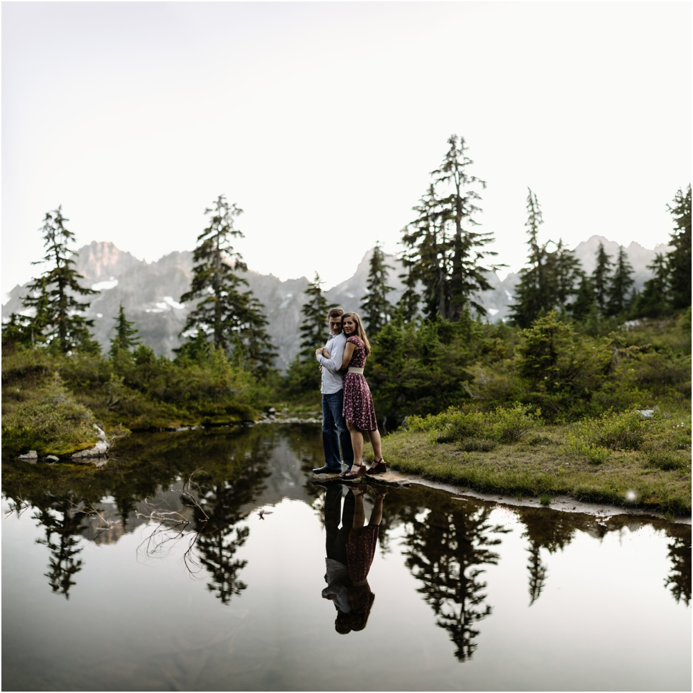 couple stands by reflecting pond PNW hiking engagement