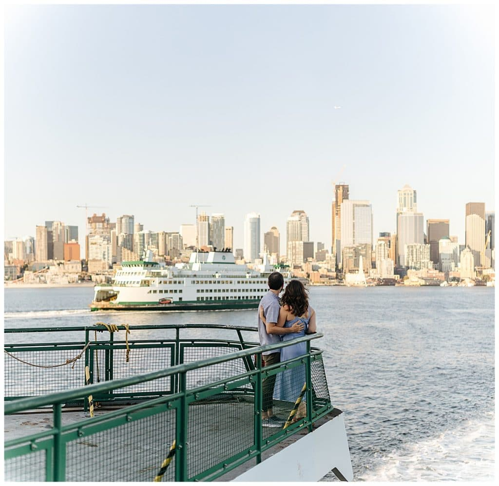 couple looks at seattle skyline Washington State Ferries engagement photos