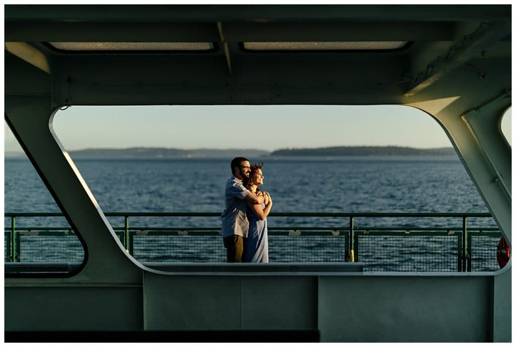 couple looks out at sunset Washington State Ferries engagement photos
