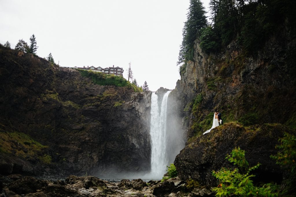 Bride and groom kiss beneath snoqualmie falls Salish Lodge weddi