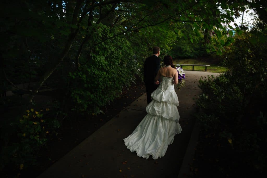 Bride and groom walk through the woods Salish Lodge wedding venu