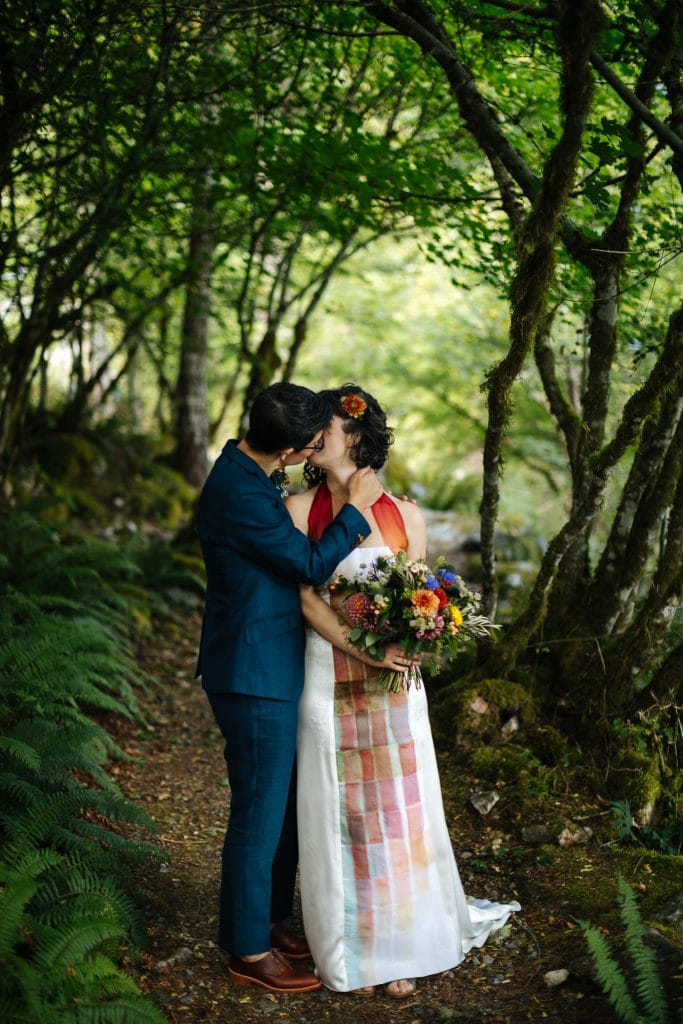 Brides kiss in the woods at a North Cascades Institute Wedding