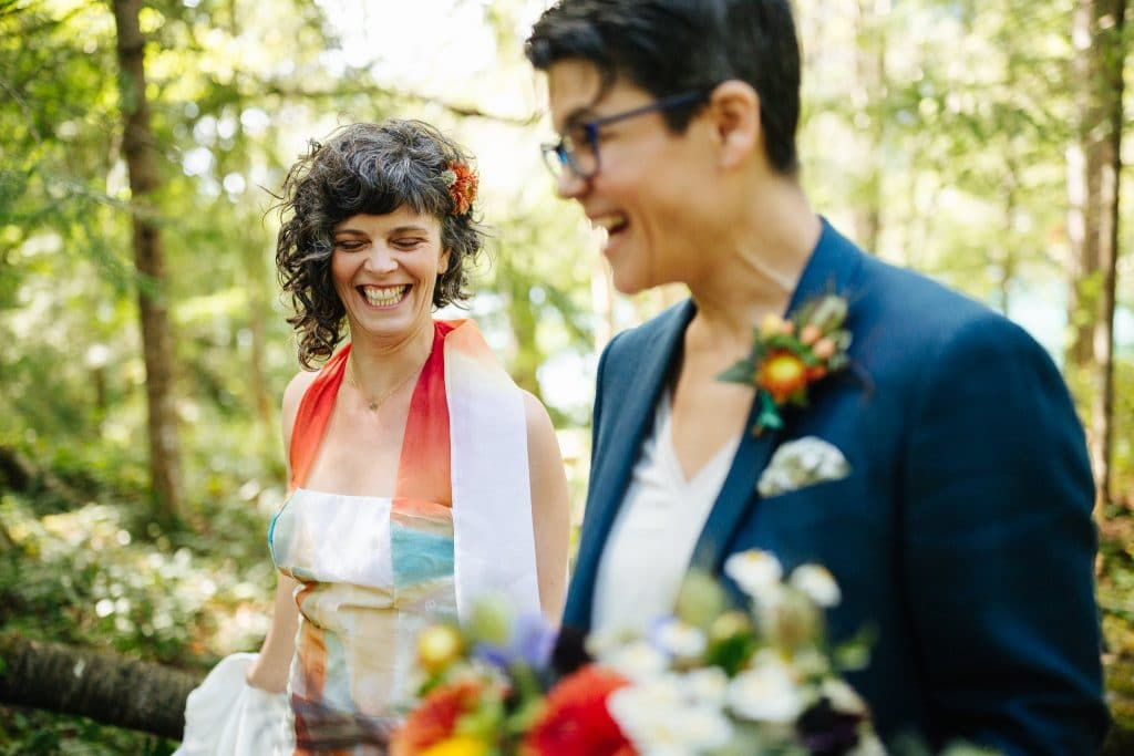 Brides laugh while walking through the woods North Cascades Inst