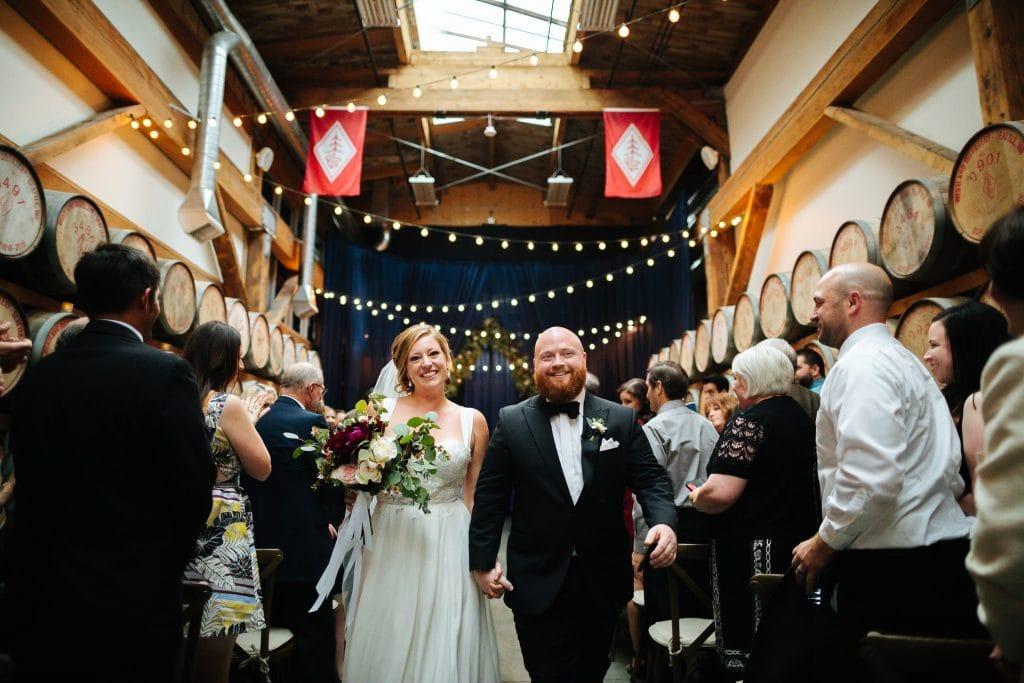 couple walks down aisle westland distillery wedding seattle venues