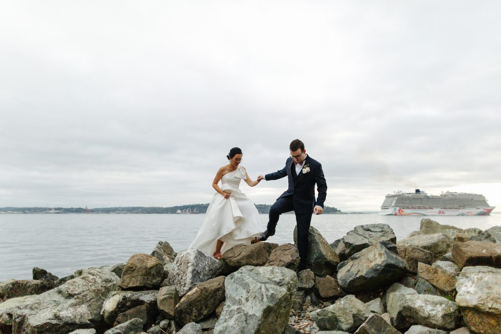 bride and groom hold hands while walking across rocks with a cruise ship