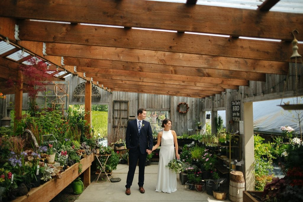 groom and bride hold hands in a greenhouse