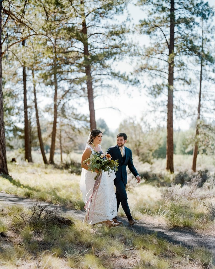 Bride and groom walk through the woods on a sunny day on a film photo