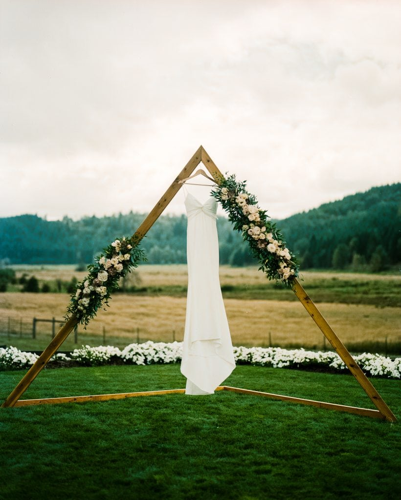 wedding dress hangs on an arch film photo