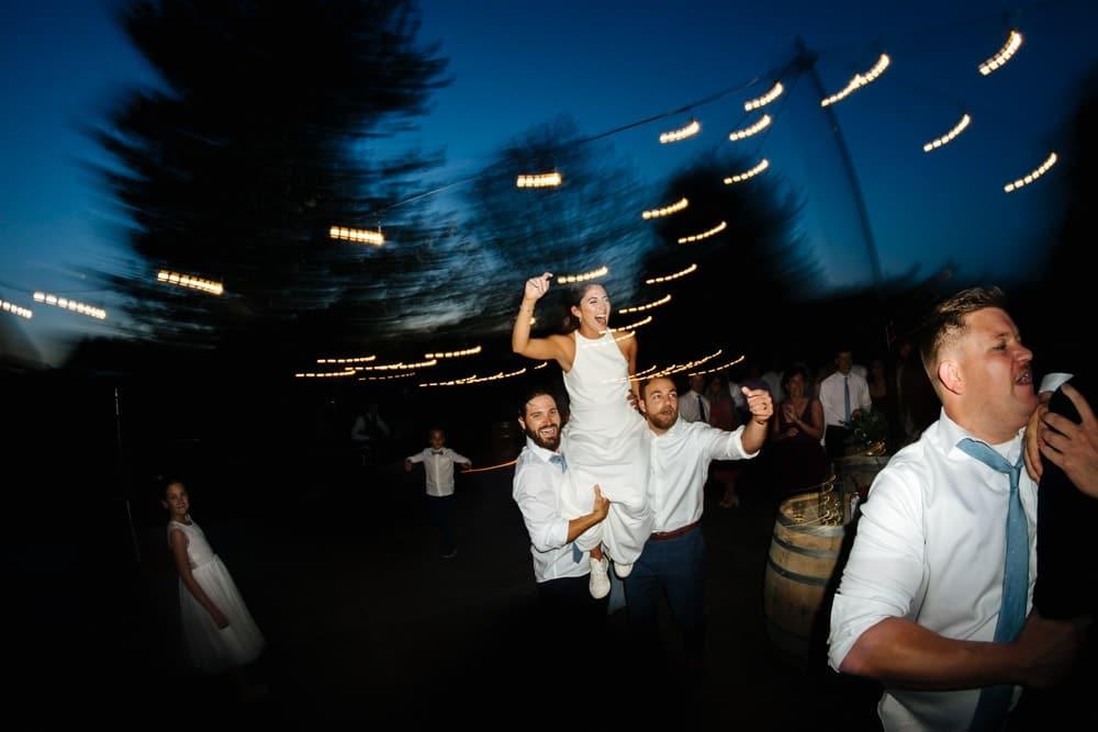 bride dances on groomsmen's shoulders at pine creek nursery wedding